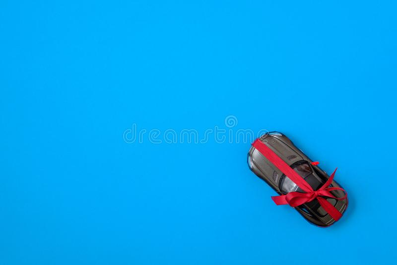 New modern car with red bow ribbon as a present. Toy car gift on blue background, flat lay composition. Top view stock images