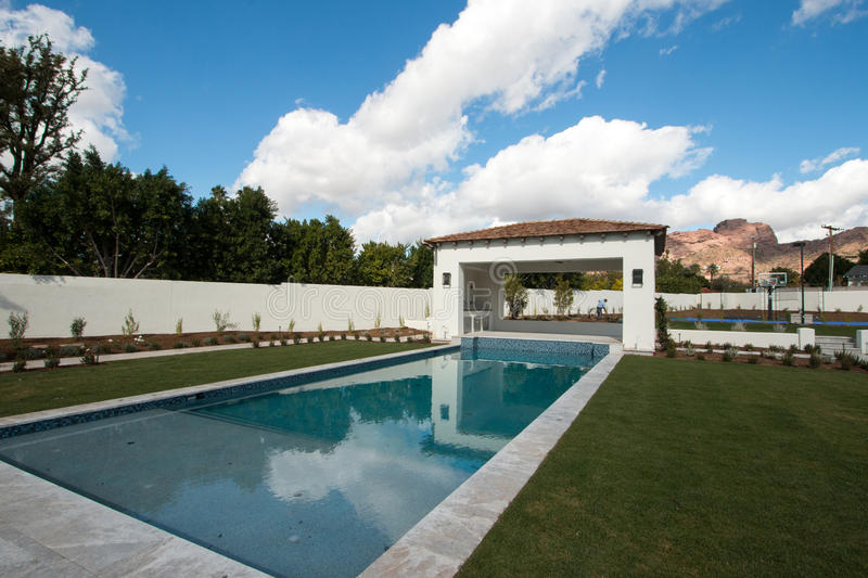 New Modern Classic Luxury Pool. Brand new enormous recreational Olympic style swimming pool and large party cabana located on huge residential property stock photos