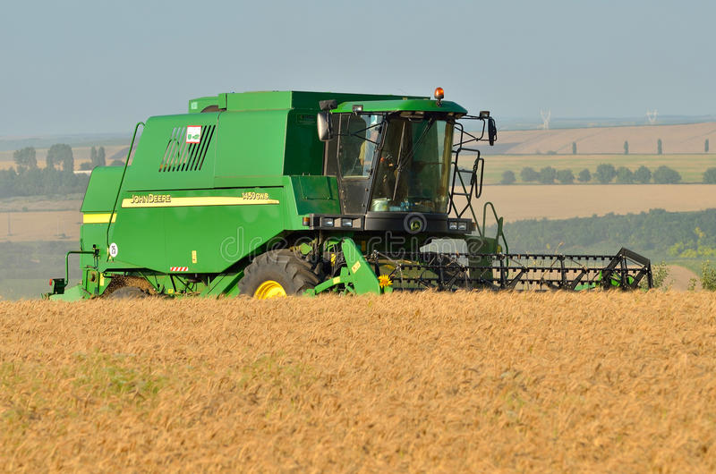 New combine harvester. John Deere big combine harvesting the wheat field in daytime. Combine harvester at work royalty free stock image