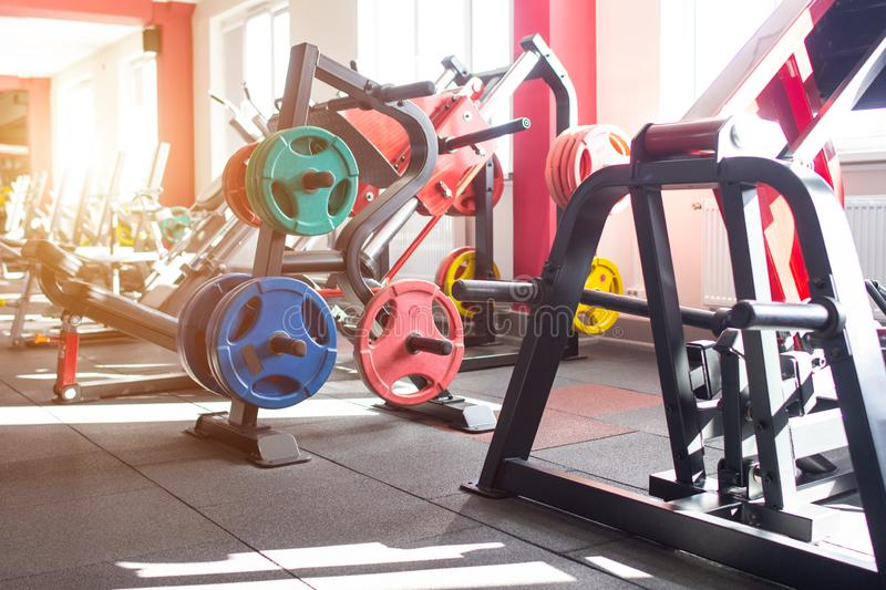 New and modern gym for sports and muscle building and strength training, multi-colored metal discs for the bar, background royalty free stock photography