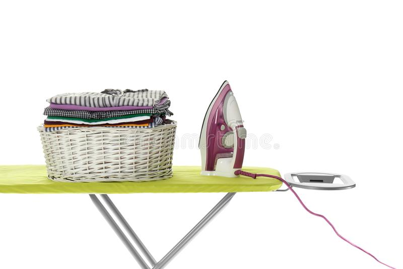 New modern iron and basket with clean laundry on board royalty free stock photography