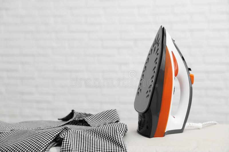 New modern iron and clean shirt on board against light background. Laundry day. New modern iron and clean shirt on board against light background, space for text royalty free stock photo