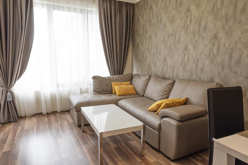 New modern living room. New home. Interior photography. Wooden floor. Sofa near the windows with long curtains stock images