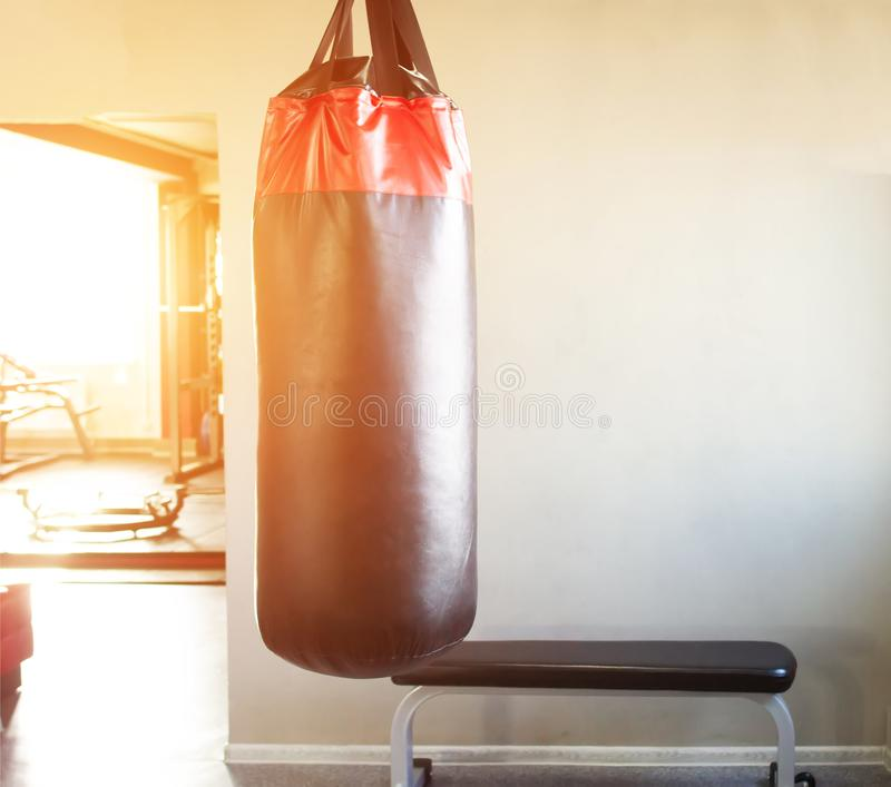 New modern punching bag in the hall for sports and martial arts on the background of the window in which the sunset, copy space stock image