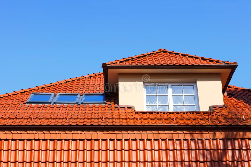 New, modern roof of red ceramic tiles, Dormer window protruding above the roof and three skylights. royalty free stock photos