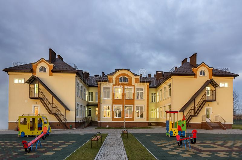 New modern two-storied kindergarten preschool building, toy bright swings on spacious yard playground with soft rubber flooring on stock image