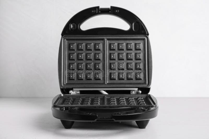 New modern waffle iron on table. New modern waffle iron on white table stock image