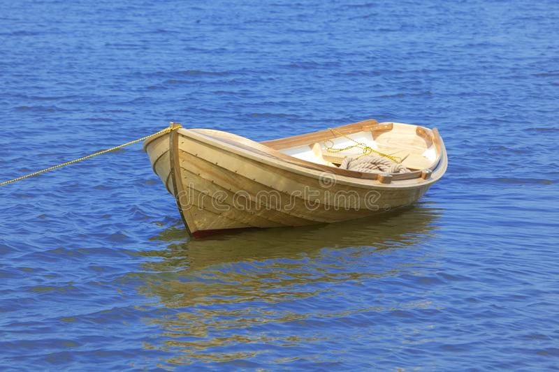 New modern wooden fishing boat in bright blue water with reflections. New modern wooden boat in bright blue water with reflections isolated on background royalty free stock image