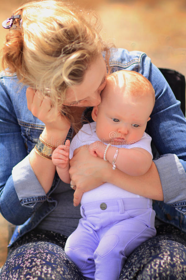 New Mom Kisses Young Baby stock photography
