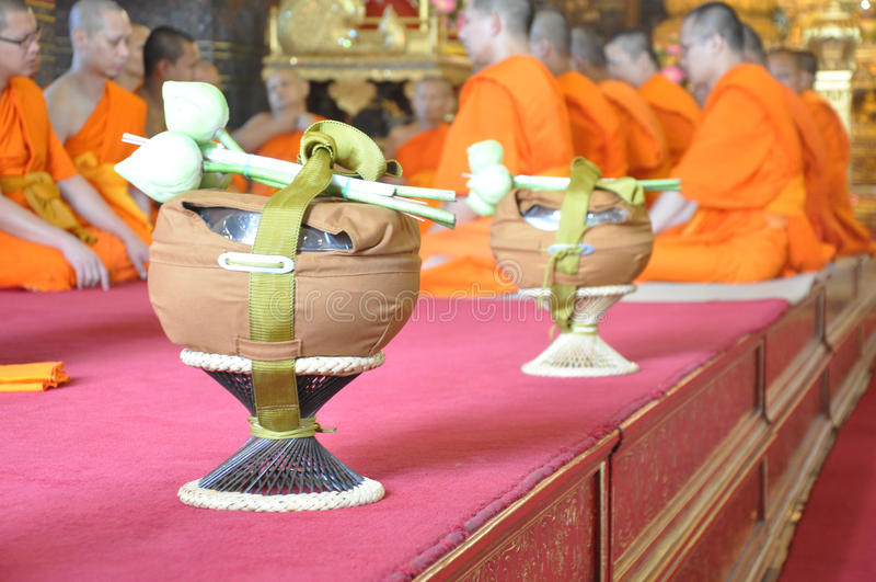 A new monk lights incense during a Buddhist ordination ceremony