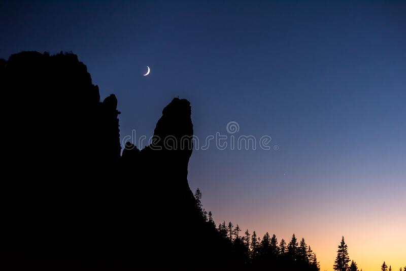 New moon over the mountains ,silhouette of tree and mountains after sunset ,twilight.  stock images