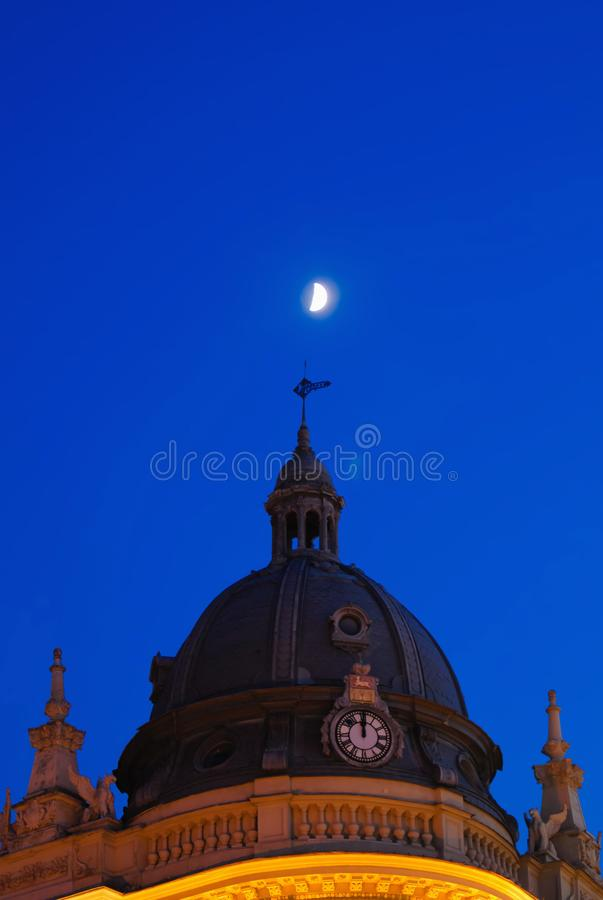 New moon shine over dome cupola in the evening clock table stock image