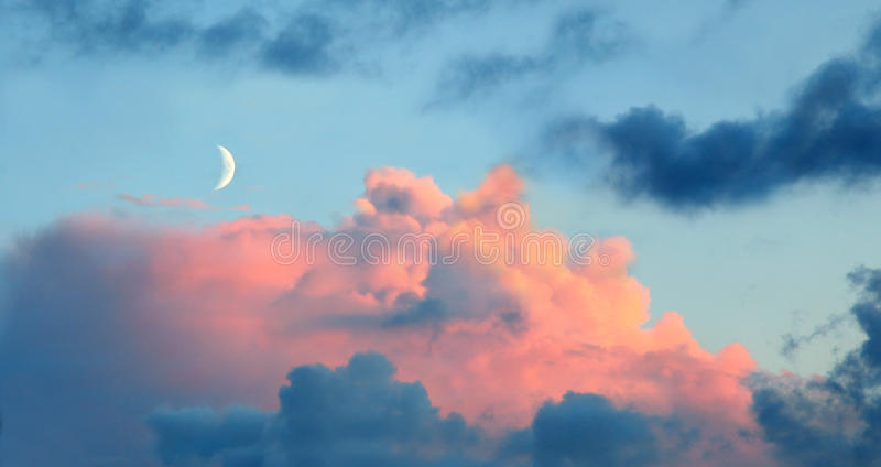New moon at sunset. With rose tinted clouds royalty free stock image