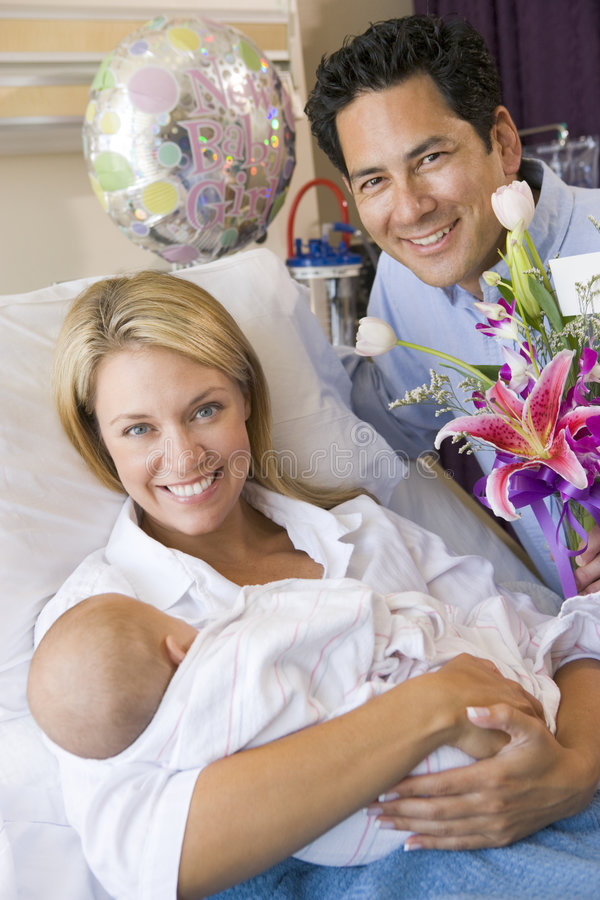 New mother with baby and husband in hospital royalty free stock images