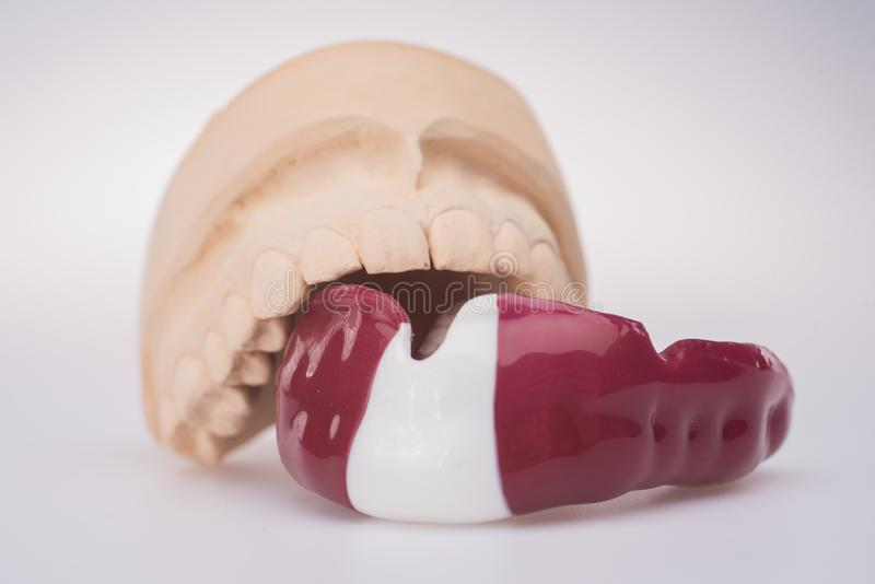 New mouth guard on a light background with latvian flag colors royalty free stock photos