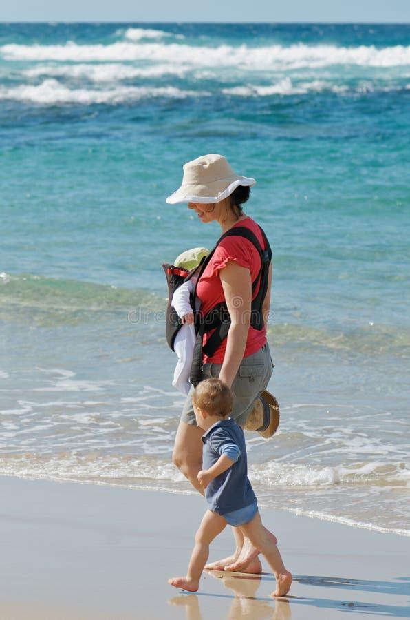 New mum walking on beach stock images