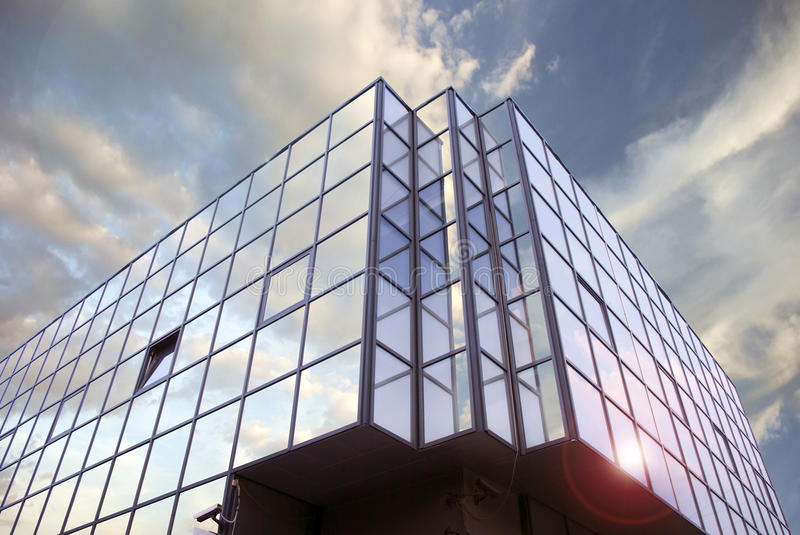 New office building. Reflection of the beautiful sky with clouds in the windows of the new office building stock image