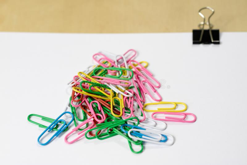 New office paper clips on a white piece of paper. Office accessories and a white sheet of paper. White background stock photo
