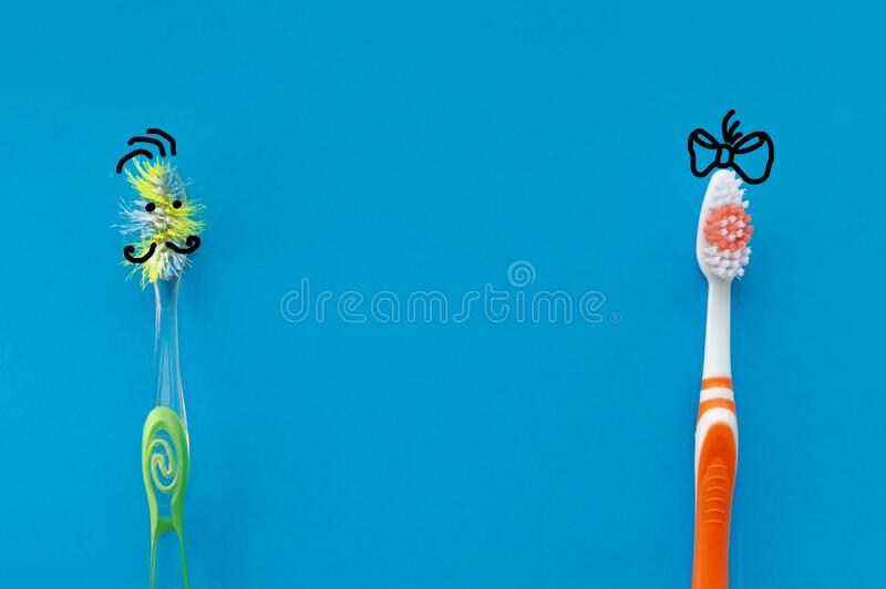New and old toothbrush in the form of cartoon characters on a blue background. The view from the top. The concept of dental health royalty free stock photos