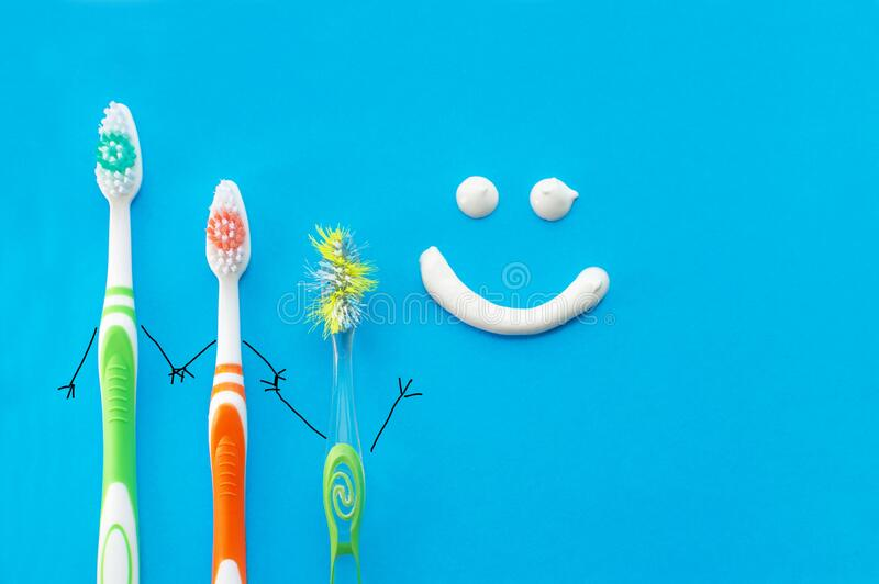 New and old toothbrushes in the form of cartoon characters on a blue background with a smile drawn with toothpaste. The view from the top.The concept of family stock image