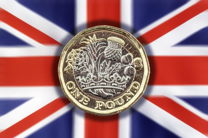 New one pound coin on a Union Jack background. New one pound coin of England UK introduced in 2017 which show emblems of each of the nations cut out and isolated stock images