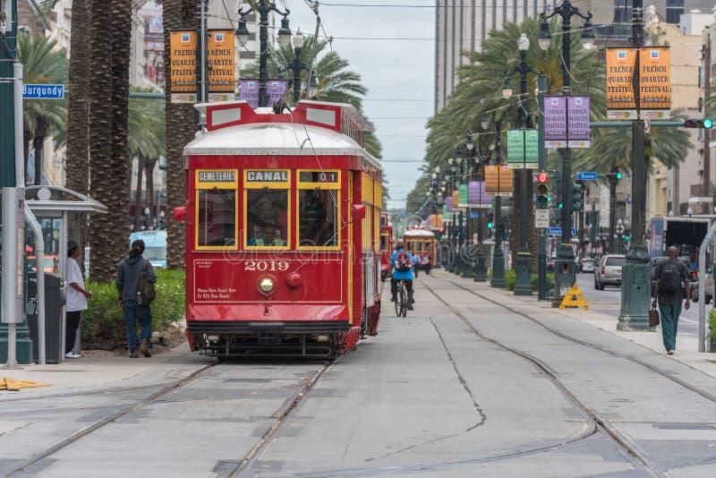 NEW ORLEANS - LA LUISIANA, L'11 APRILE 2016: Citiscape di New Orleans con il tram e la gente Le biciclette, i cavalli di carretto immagine stock