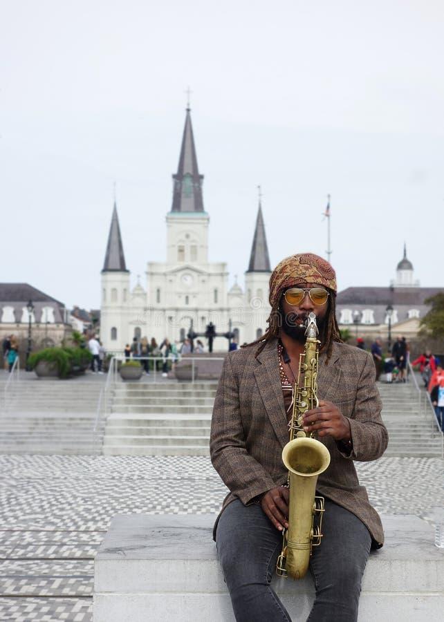NEW ORLEANS LA/USA -03-17-2019: En musiker spelar jazz på saxofonen framme av St Louis Cathedral i franska New Orleans royaltyfri bild