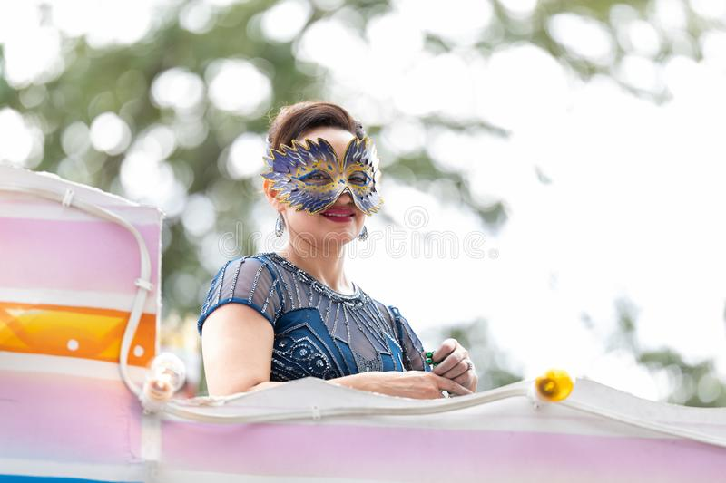 Mardi Gras Parade New Orleans. New Orleans, Louisiana, USA - February 23, 2019: Mardi Gras Parade, Woman wearing traditional clothing, throwing beads to the stock image