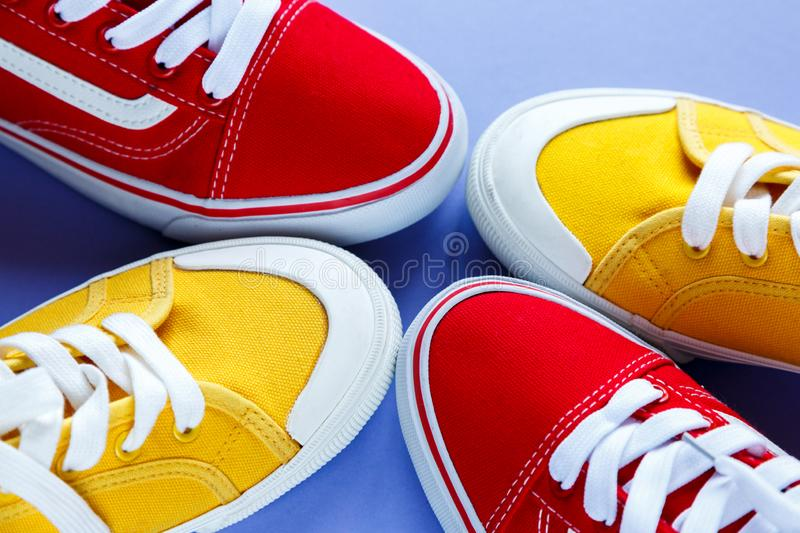 New pair of red and yellow sneakers on violet background . Lifestyle  sneakers stock image