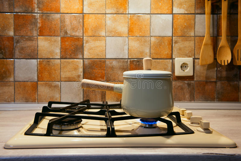 New pan with wooden handle on the stove. On fire stock photos