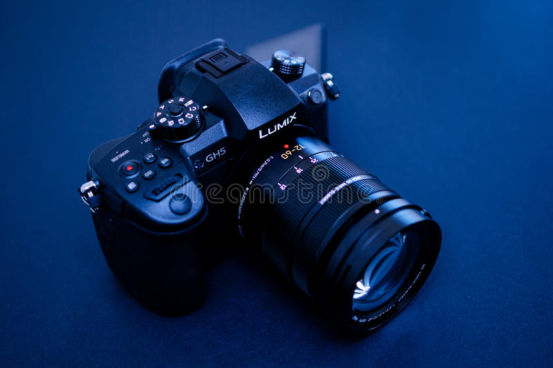 New Panasonic Lumix GH5 and Leica 12-60 camera lens. PARIS, FRANCE - APR 9, 2017: Blue tone view detail of the Panasonic Lumix DMC-GH5 - and Leica Vario-Elmarit royalty free stock image
