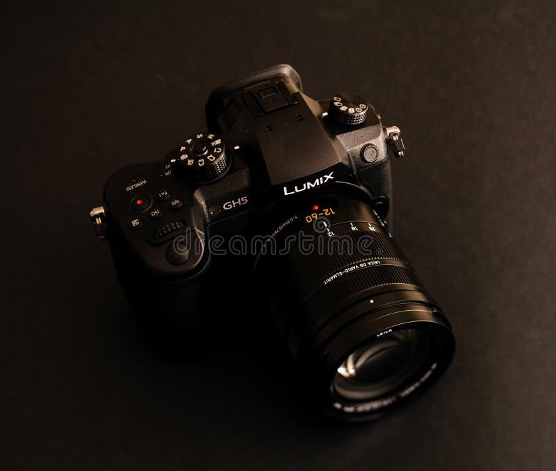 New Panasonic Lumix GH5 and Leica 12-60 camera lens. PARIS, FRANCE - APR 9, 2017: view detail of the Panasonic Lumix DMC-GH5 - and Leica Vario-Elmarit 12-60 royalty free stock photography