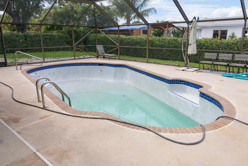 New pool filling with water. Resurfaced Diamond Brite pool plaster now being filled stock photography