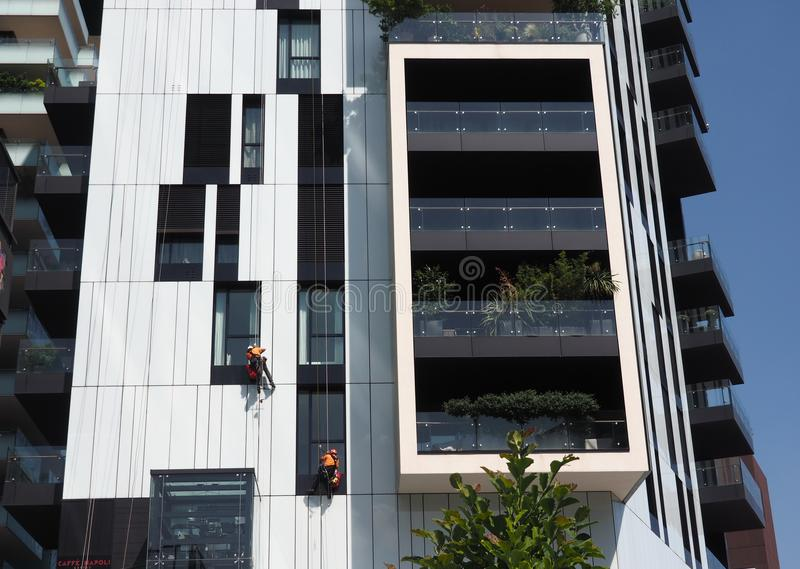 MILAN, ITALY, JUNE 3 2018: New Porta Nuova district,worker cleaning windows and glasses of tower hanging on the rope. New Porta Nuova district,worker cleaning stock photo