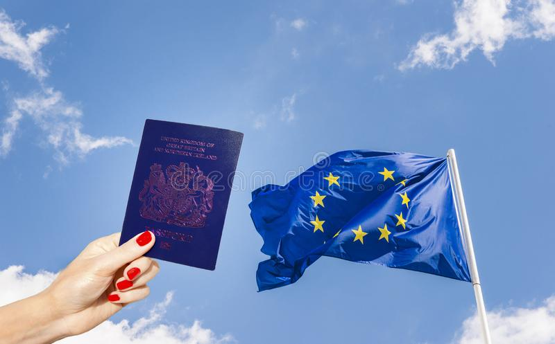 New post-Brexit blue UK passport with European Union flag minus one star against a blue sky royalty free stock photo