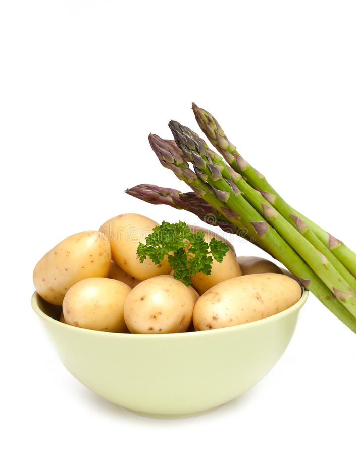 New potatoes and green asparagus royalty free stock image