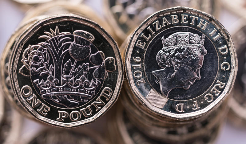 New pound coin introduced in Britain, front and back. With background of coins stock photo