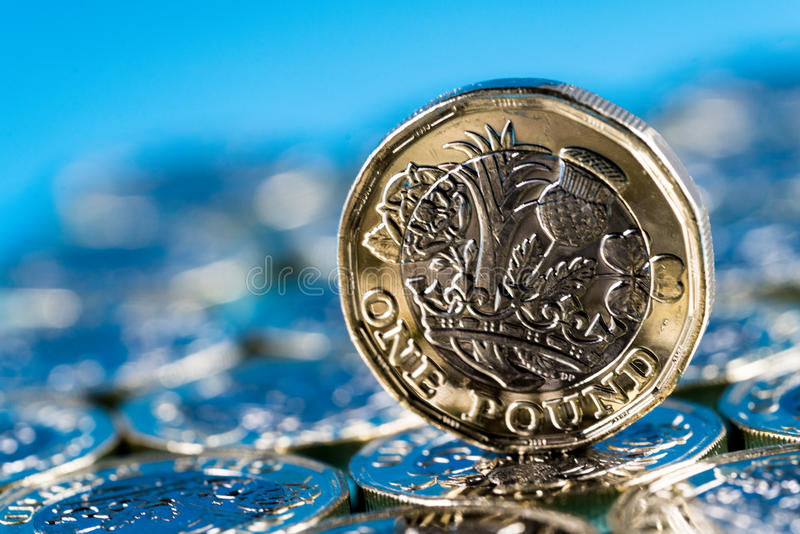 New pound coin introduced in the UK in 2017, front, standing on a layer of coins and on a blue background. New pound coin introduced in Britain in 2017, front stock photos