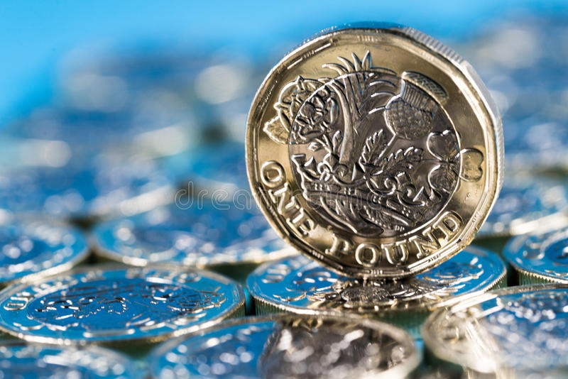 New pound coin introduced in the UK in 2017, front, standing on a layer of coins and on a blue background. New pound coin introduced in Britain in 2017, front royalty free stock images