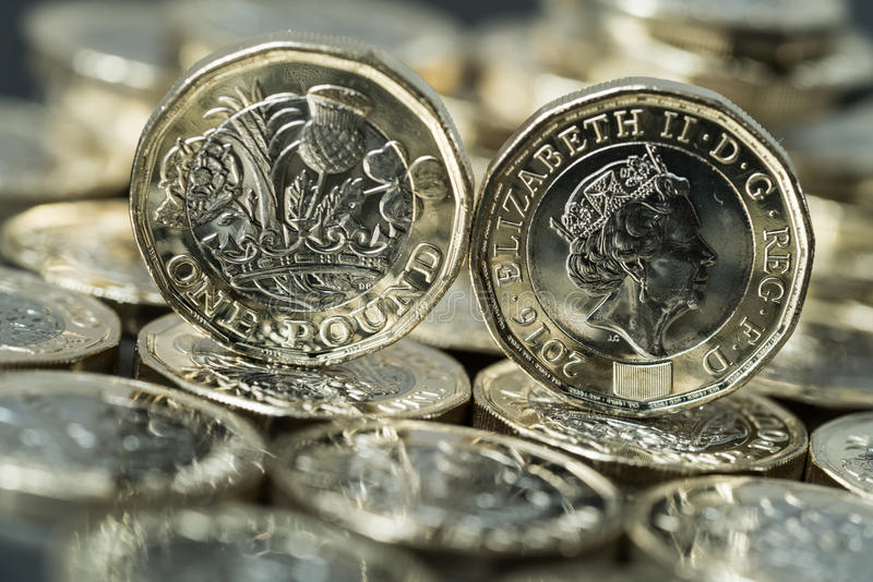 New pound coins introduced in Britain in 2017. New pound coin introduced in Britain in 2017, front and back, standing on a layer of coins stock image