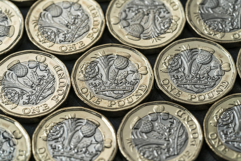 New pound coins introduced in Britain in 2017. Layer of new pound coins introduced in Britain in 2017, on a black background stock images