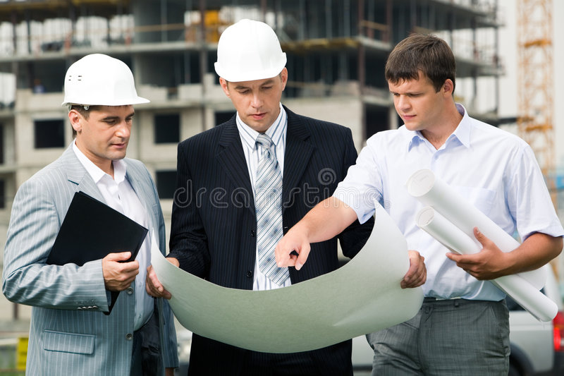 New project. Portrait of three builders standing at building site and discussing new project held by one of men royalty free stock image