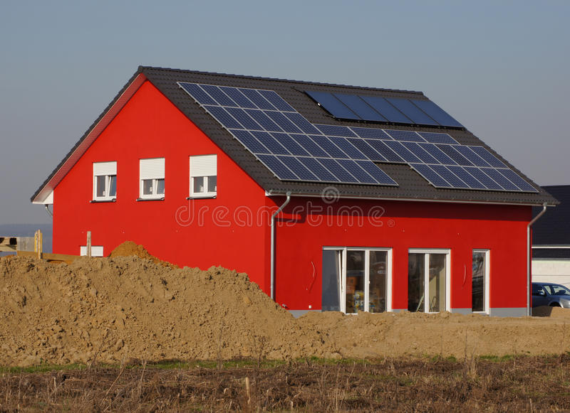 New red house. New house with solar cells on the roof royalty free stock images