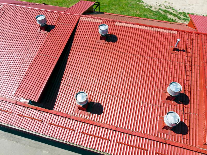 New red metal warehouse roof with installed pipes of ventilation. Systems. aerial photo royalty free stock photo