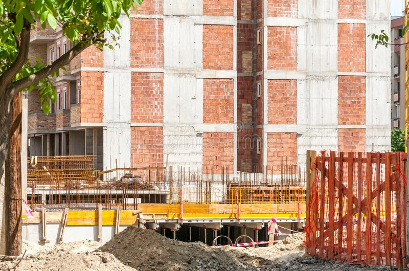 New residential building construction site entrance with gate of safety net fence with view on the concrete and metal reinforcemen royalty free stock photography