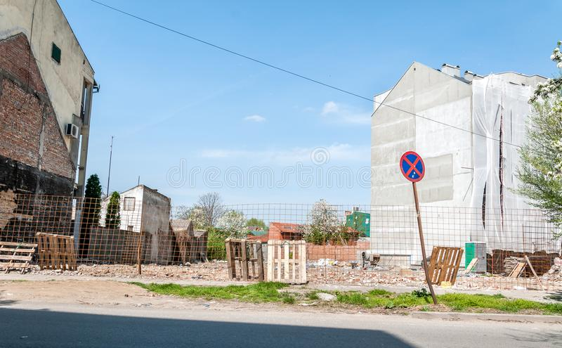 New residential building preparation of construction site land in the city with safety barrier and fence around the empty lot royalty free stock photo