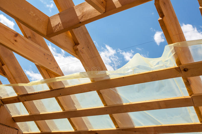 New residential construction home framing against a blue sky. Roofing construction. Wooden construction. New residential construction home framing against a royalty free stock photography