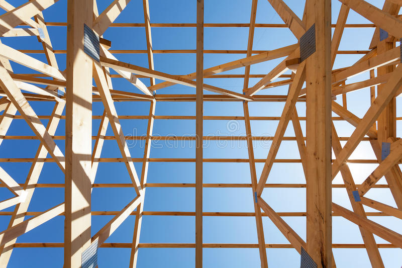 New residential wooden construction home framing against a blue sky. royalty free stock photos