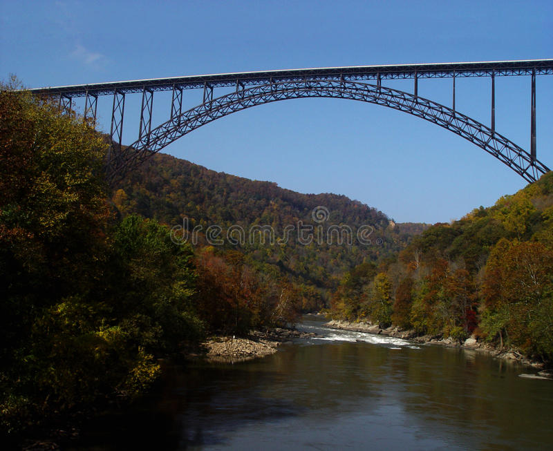 New River Gorge Bridge, WV on Fall Day. The immense, steel-arch, New River Gorge Bridge in West Virginia spans the river below. The tallest, single arch, steel royalty free stock photo