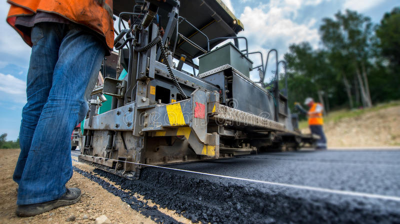 New road construction. Paving new road with asphalt, road construction stock images